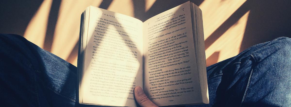 Nærbillede af person, der holder en bog slået op på en side
