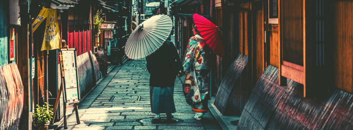 To kvinder med paraplyer på en gågade i Kina