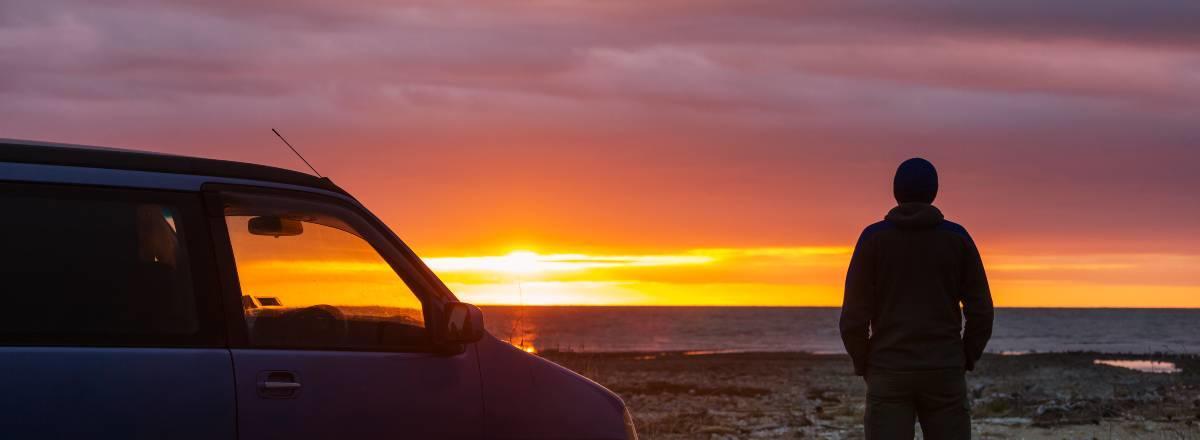 mand ved siden af bil kigger på solnedgang