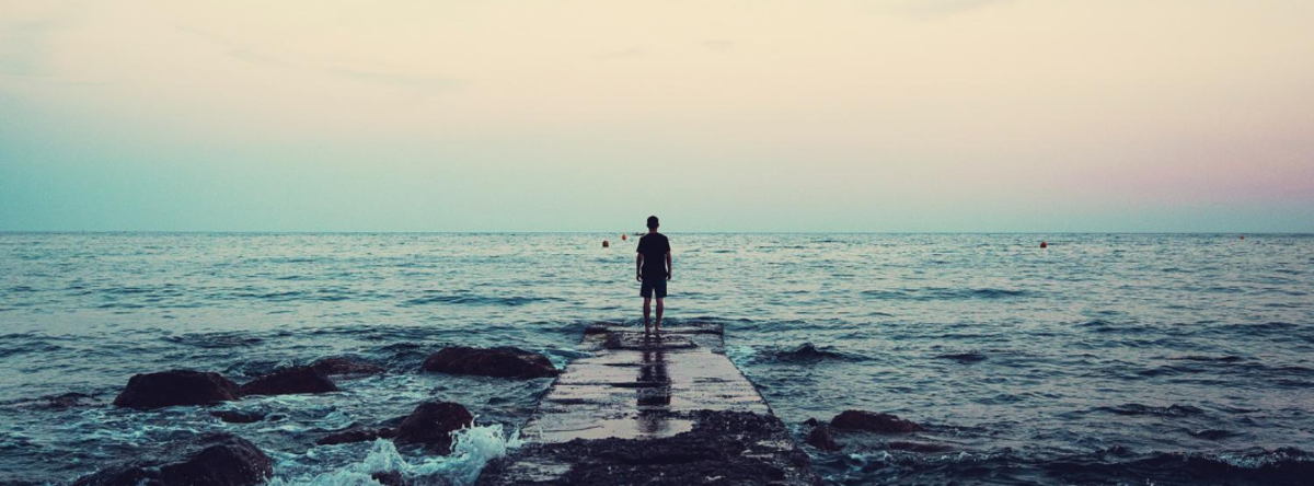mand kigger udover horisonten ved havet