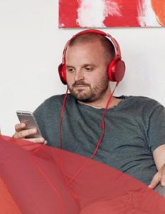 Mand sidder i sofa og lytter til lydbog