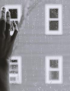 Nærbillede af en hånd på en regnfyldt rude