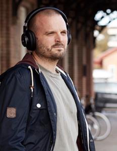 Mand med høretelefoner venter på tog