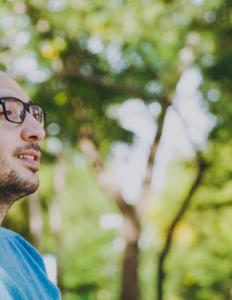 ung mand lytter med hørebøffer i solskin