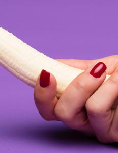 kvindehånd, der holder en skrællet banan