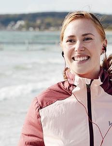 Kvinde på strand med lydbog