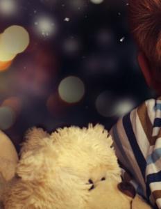 Billede af en dreng og hans bamse, der kigger ud af vinduet